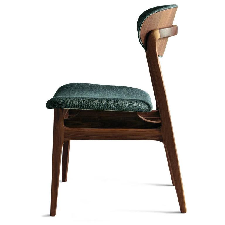 This elegant chair features a structure in solid Canaletto walnut wood with a natural or grey finish executed with natural oils. The cushions for seat and back can be covered with leather or fabric.