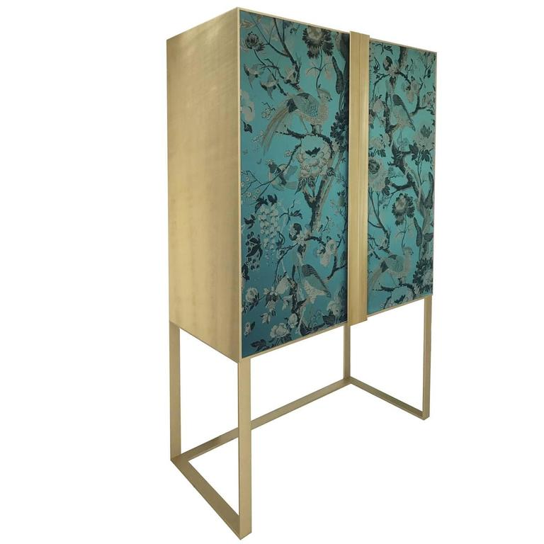 This sophisticated cabinet will complement any decor, thanks to its Minimalist Silhouette and the noble materials used. Its timeless allure is given by the brushed brass structure and handles that elegantly frame the cabinet doors in wood entirely