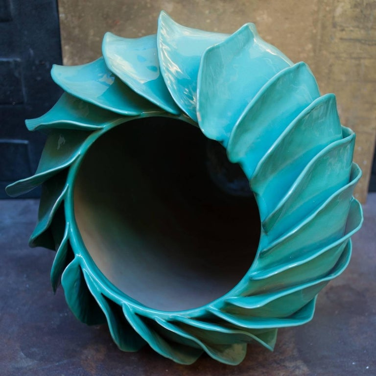 This remarkable vase is part of a limited series of numbered pieces all signed by the artist. This piece features a glossy aqua-green glaze and a truly captivating shape resembling the petals of a flower that is about to bloom. Because it is made by