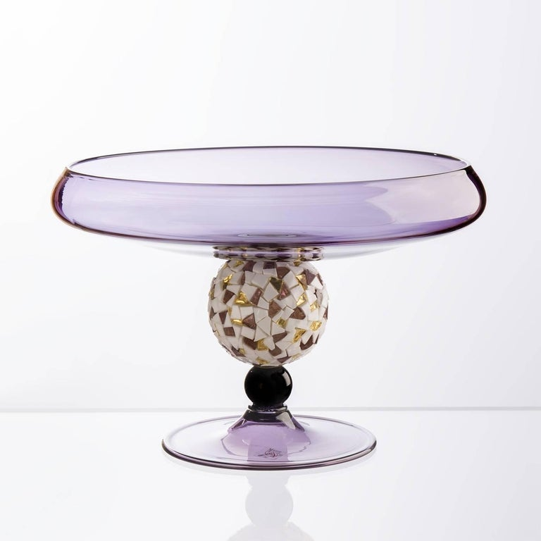 This exquisite centerpiece is made of Murano mouth-blown glass in amethyst color and features a pedestal with a small glass sphere in the same amethyst color surmounted by a large crystal sphere covered with a mosaic of tesserae made of 24-karat