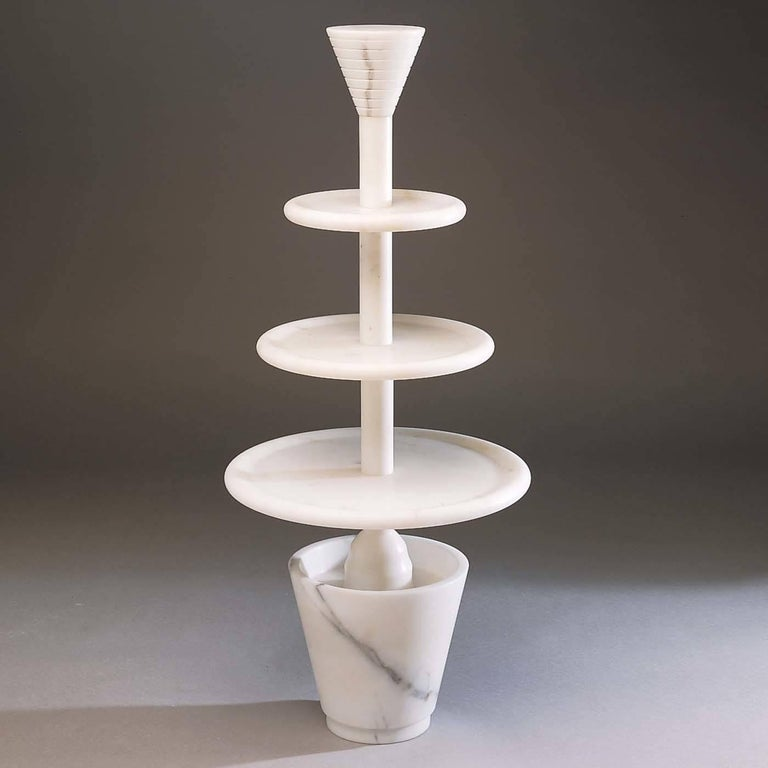 An immaculate design that conveys the high aesthetic quality of marble with its bare, monochromatic Silhouette. Designed by Ugo La Pietra in 1987, this striking three-tier cake stand is a unique way to serve hors d'oeuvres, fruit, or desserts in