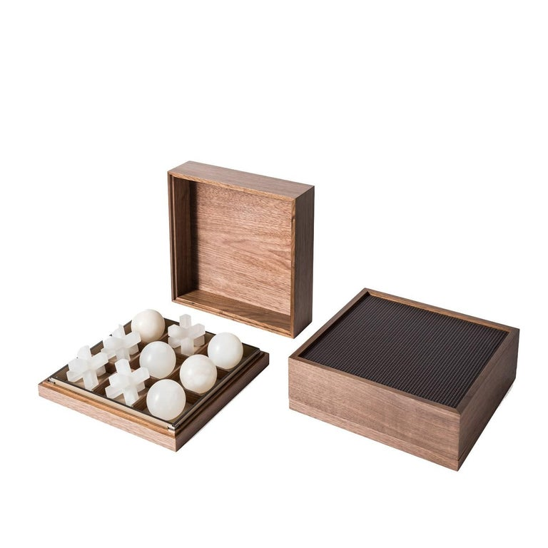 Traditional craftsmanship and noble materials make this game box the ultimate sophisticated accessory. A perfect gift and a precious addition to any home, this box is made of wood with the top of the lid upholstered in leather. The alabaster noughts