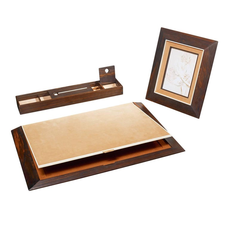 This elegant desk pad in ebony wood has a shutter covered in nubuck leather and it is highlighted at the edges with a horn frame. The interior is finished with a contrasting color.