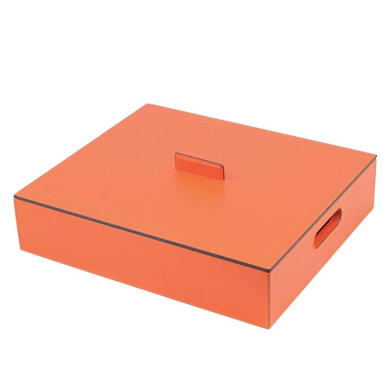 This striking case is an elegant addition to any playroom and will add a splash of color and sophisticated luxury to any home. The wood box is entirely covered in leather with a bright orange color. It features a handle for the box and one for the