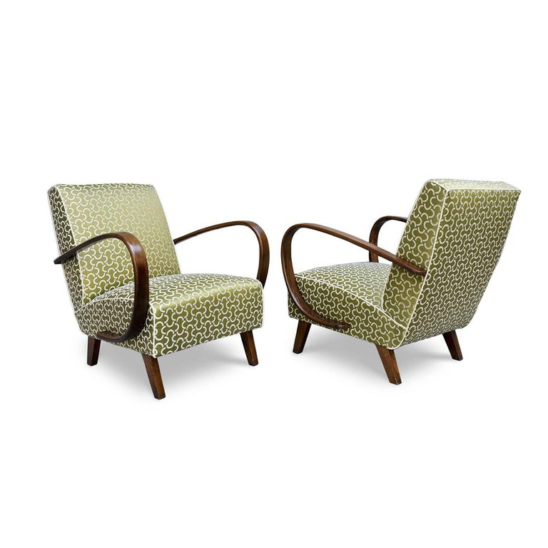 This charming armchair is part of the Art Deco collection. The structure in beechwood features striking armrests that were curved using steam and it is completed by jute straps, iron double-cone-shaped springs, vegetable fibers, and cotton wadding.