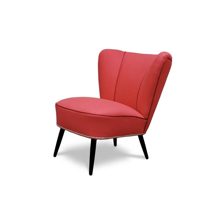This chic cocktail chair was handcrafted using traditional methods and durable materials for a long-lasting object of functional decor. The slightly slanted legs, a homage to mid-century design, are turned by hand in beechwood and painted in a dark,