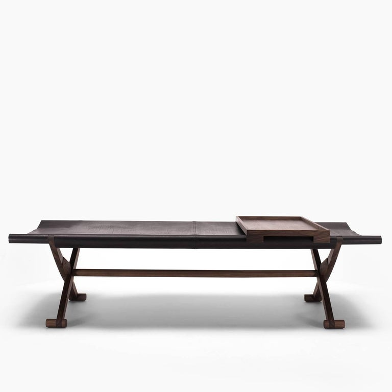 The origins of this product are as old as time, and most likely this was once a travel bed. This bench is made of solid black hickory, with a seat in full-grain leather. Branda can be folded for storage when not in use.