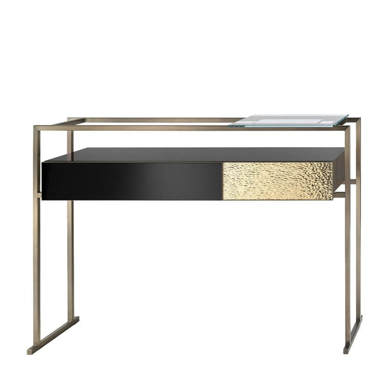 This stately console features a rectangular element with two drawers: one with a black glass door, and the other made of golden mirrored glass with