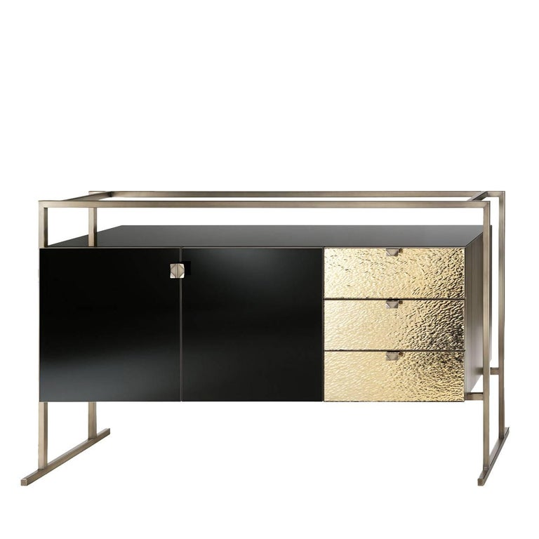 A minimalist tube-shaped metallic structure made of antiqued and bronzed brass, highlighted with a delicate brushed finish, frames this striking piece. The central element features two black glass doors and three mirrored glass drawers with golden