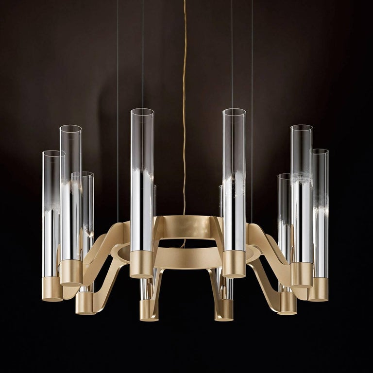 Designed by Giovanni Luca Ferreri, this imposing chandelier features a circular metallic frame, made of bronzed brass with a matte gold finish from which ten curved arms extend holding tubular lighting elements. Each element is exquisitely crafted