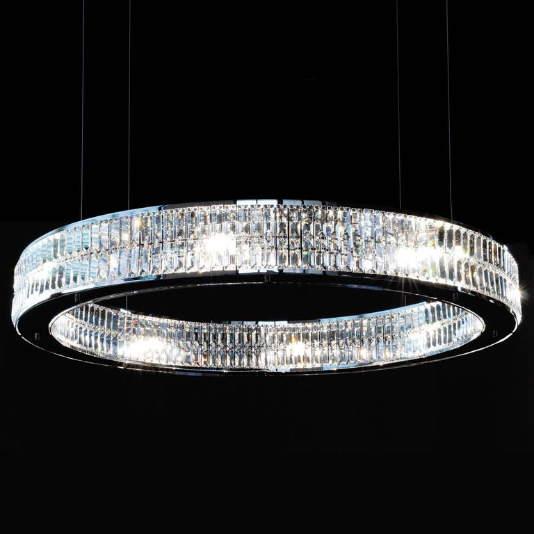 A lavish piece of functional decor, this chandelier will be a sumptuous and modern accent in a contemporary home as well as a classic interior. The ring that constitutes its shape is made up of two layers of handmade crystal prisms attached both