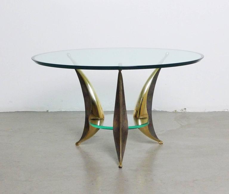 Significant Italian coffee table with two plates and three massive brass feet from the 1950s. The skillful design of the elegant swung brass feet, gripping and bearing the glass, reminds on the work of a sculptor. Each case leg has a polished