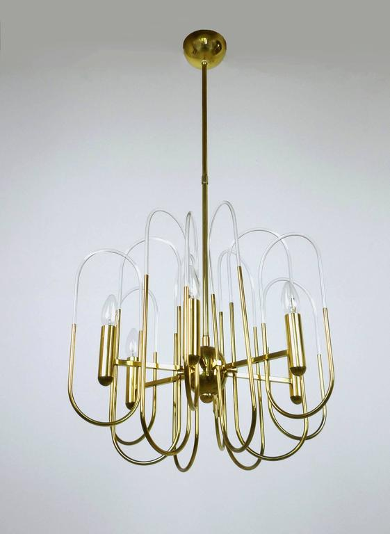 Gaetano Sciolari designed this elegant chandelier in the 1960s for his family business Sciolari Lighting in Italy. The complex structure of his sophisticated chandelier features twelve oval loops in different heights fixed to 12 square rods, which