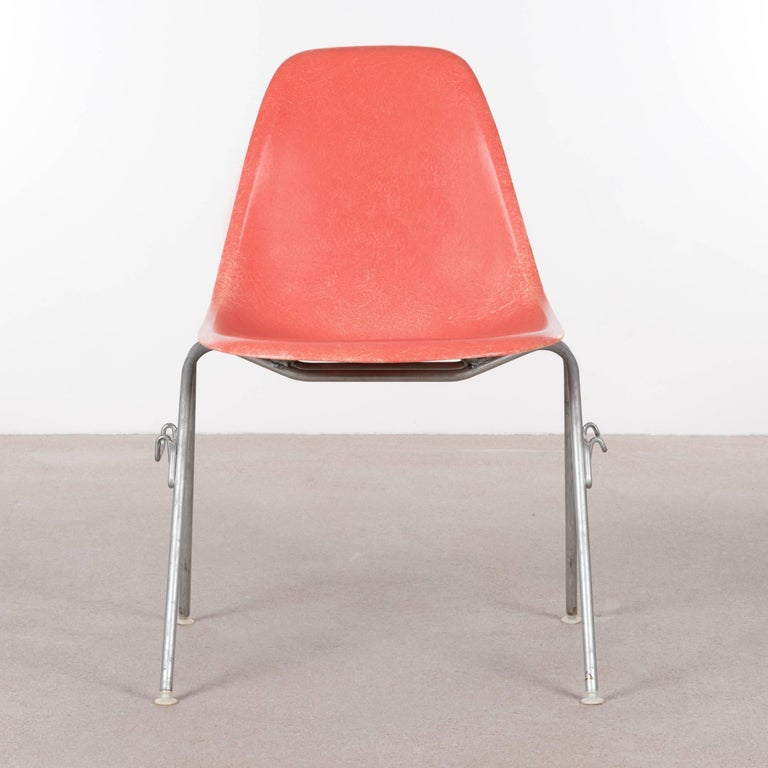 Iconic DSS (D)ining height (S)ide chairs with (S)tacking base in Salmon. The fiberglass shell is in very good vintage condition with only slight traces of use. Original zinc-plated steel base also in very good condition. The chairs are signed patent