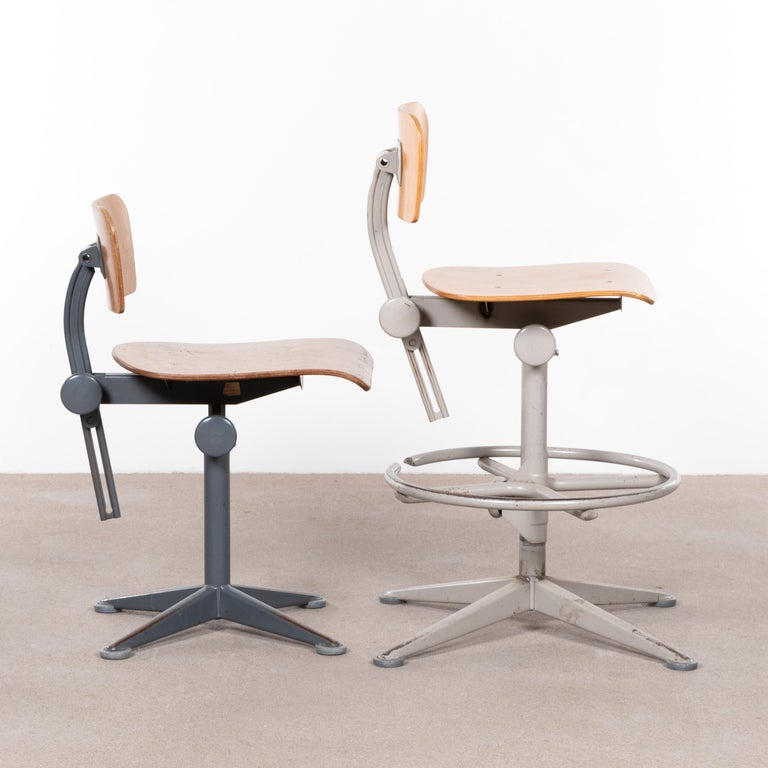 Functional and industrial drafting stools (arhitect stools) by Friso Kramer. The stools are adjustable in seating height and swivel. Good vintage condition with steel bases and plywood seats / back rest. Signed with impressed manufacturer's