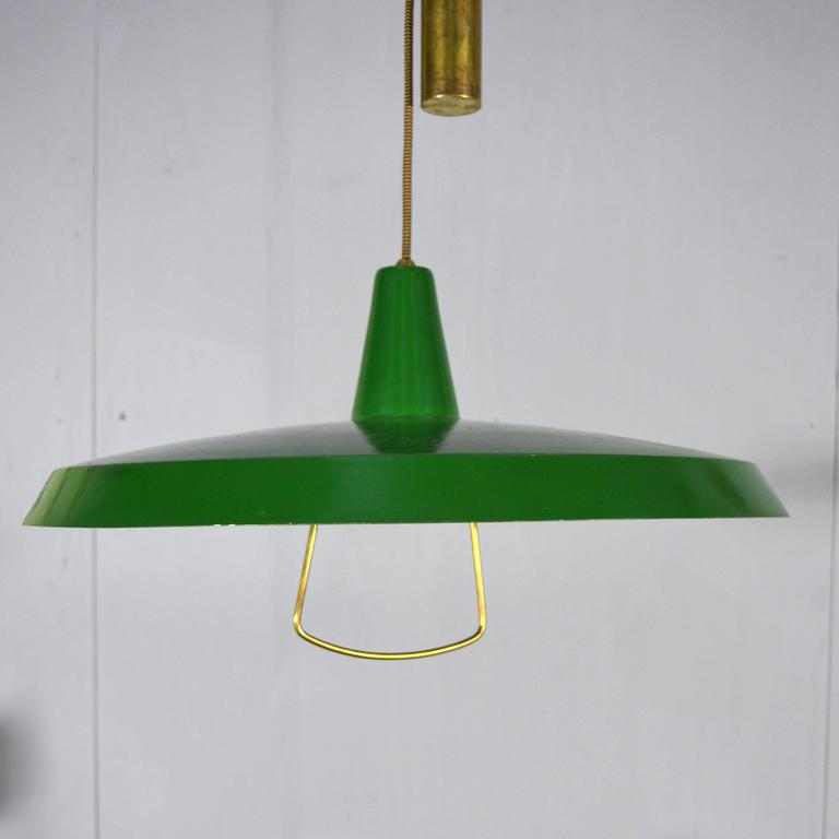 Gorgeous counter balance pendant lamp with brass counterweight and other brass details.