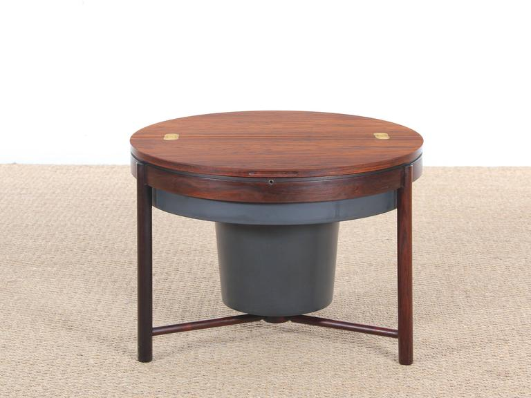 Rosewood coffee bar table and Rolf Adolf Relling Rastad in 1962. Consituée a circular plate whose moitiée gets up and opens on a rotating casing Publisher accommodate glasses and bottles . This highly original and ingenious system first designed for