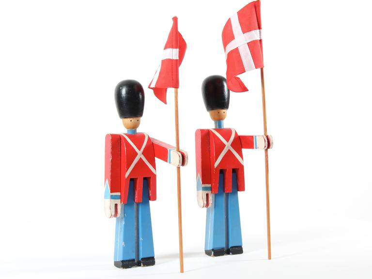Guard Royal flagship, Danish Royal Guard with flag Kay Bojesen.  Kay Bojesen whose small shop is installed near the royal residence, sees passing everyday the Royal Guard. In 1940, after the entry into little Denmark, Bojesen created in support of