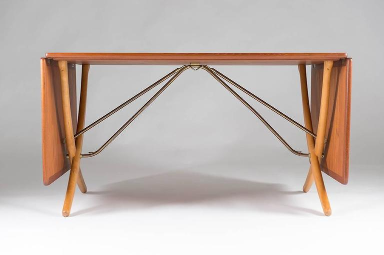 Rare drop-leaf table AT-304 by Hans J. Wegner for Andreas Tuck. This stunning dining table is made of teak with legs of birch. The drop leaves are held by brass rods that lock automatically when you pull up the leaves; function and design in true