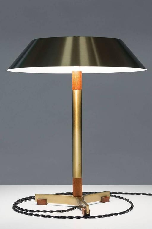 """Scandinavian Mid-Century table lamp model """"President"""" by Jo Hammerborg for Fog & Mørup in Denmark. This beautiful table lamp features two light sources and is made of solid brass with details of teak. The lamp is in very good vintage condition with"""