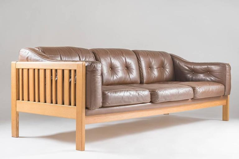 Top-quality sofa designed by Ingvar Stockum for Futura Möbler in 1965. This sofa was only in production for two years because production costs were too high. The sofa is made of solid oak, and leather cushions filled with polyethylene. This sofa is
