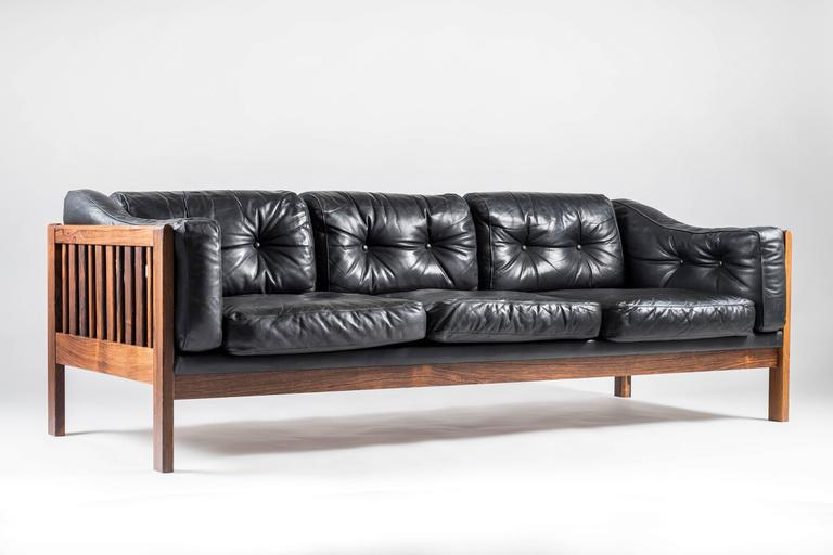 Top-quality sofa designed by Ingvar Stockum for Futura Möbler in 1965. This sofa was only in production for two years because production costs were too high. This luxury version with its frame made of solid rosewood and black leather cushions filled