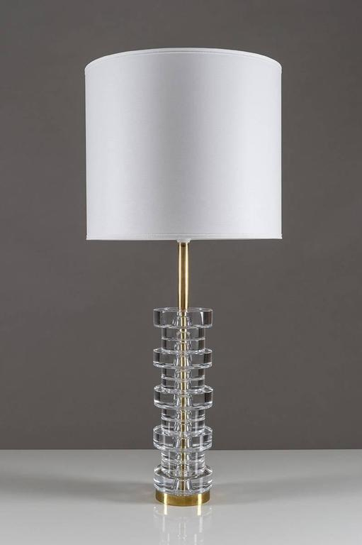 A pair of magnificent table lamps by Carl Fagerlund for Orrefors, Sweden. The lamps consist of 13 discs made of clear crystal glass, resting on a base of brass. The lamps are the largest version of this model. Condition: The lamps are in very good