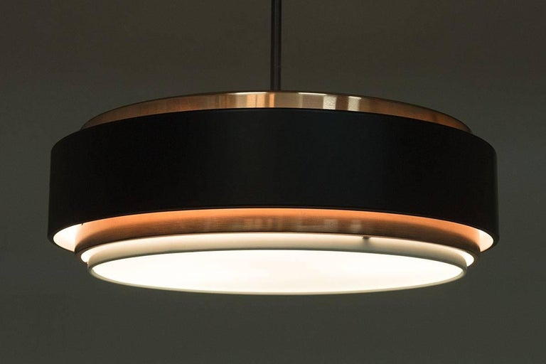 A Danish midcentury pendant by Jo Hammerborg for Fog & Mørup. The pendant features three-light sources fitting E-27 bulbs, giving a warm cozy light.