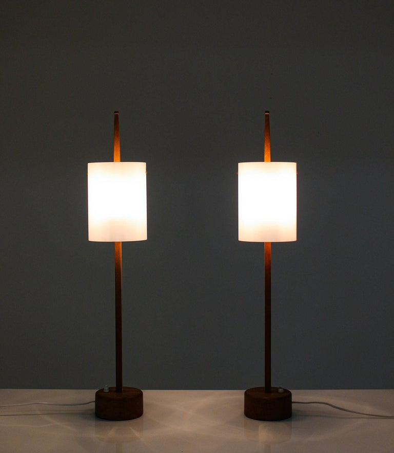 Rare pair of table lamps by Uno & Östen Kristiansson for Luxus.  The lamps consist of two light sources, hidden by an acrylic shade. The shade rests on an oak pole, which sits on a thick wooden foot with a heavy iron plate on the bottom. Very high