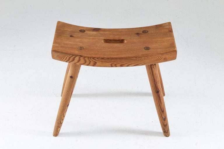 A stool in pine produced in Sweden, 1940s. A great example of the sports cabin furniture that was produced in Sweden between 1930-1960. This anonymous stool is made of solid pine with beautiful shapes and details. Condition: Very good original