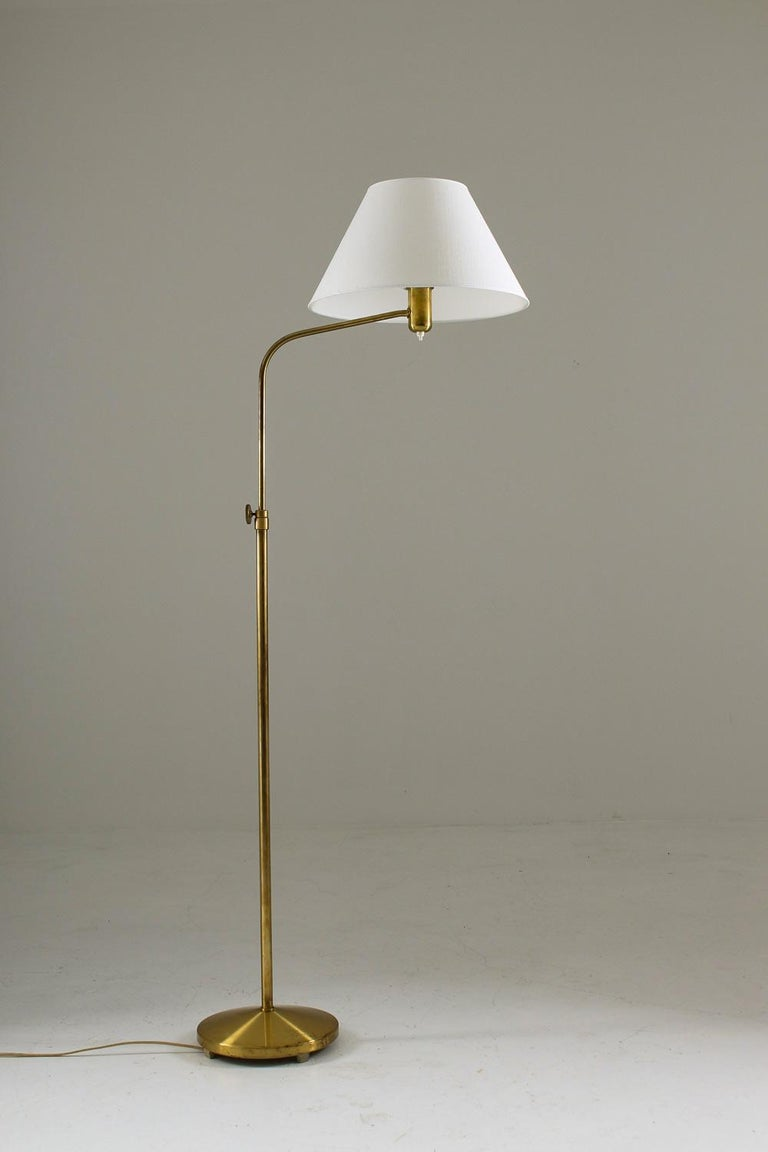 Floor lamp manufactured by ASEA, Sweden, 1940s. Beautiful floor lamp in solid brass with adjustable height. Perfect for having beside a sofa as you can swivel the part that is holding the shade.  Measures: Height 150-180cm Condition: Good