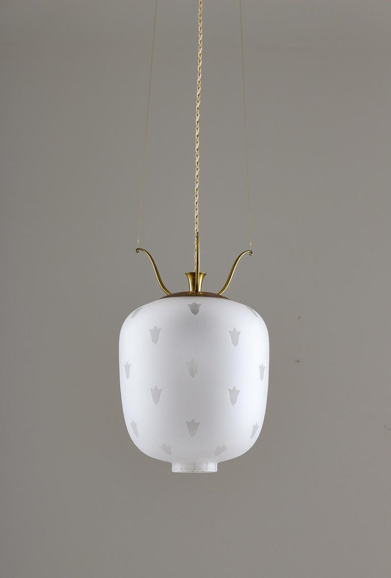Elegant pair of pendants in brass and blasted glass produced in Sweden. The frosted glass gives a beautiful and soft light and the brass parts have a soft natural patina. The lamps hang from three twisted brass wires that are fixed on the top brass