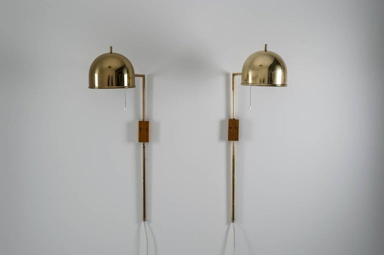 Set of four wall lamps in brass, model V-75 designed by Eje Ahlgren for Bergboms.  The rod is held by a wooden block and the height can be adjusted.  Condition: Very good vintage condition, minimal dents on two of the shades (impossible to catch