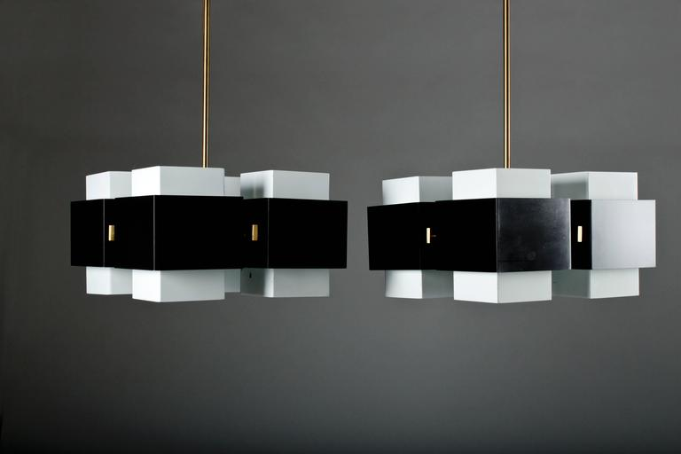 Pair of rare chandeliers by Hans-Agne Jakobsson for Markaryd in white and black painted metal, and a grounded brass inner frame and pendulum. The pendulum can be made to desired length. (The length below -130cm- is the lamp including the pendulum.