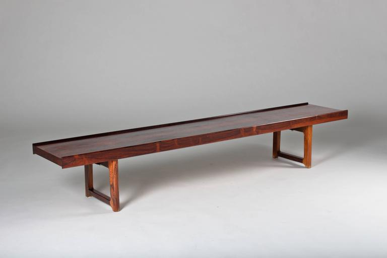 Krobo bench by Torbjørn Afdal in dark rosewood. This bench was covered in a blanket that was attached to the underside by the previous owner. Therefor the surface is in original near mint condition, not even bleached by the sun.