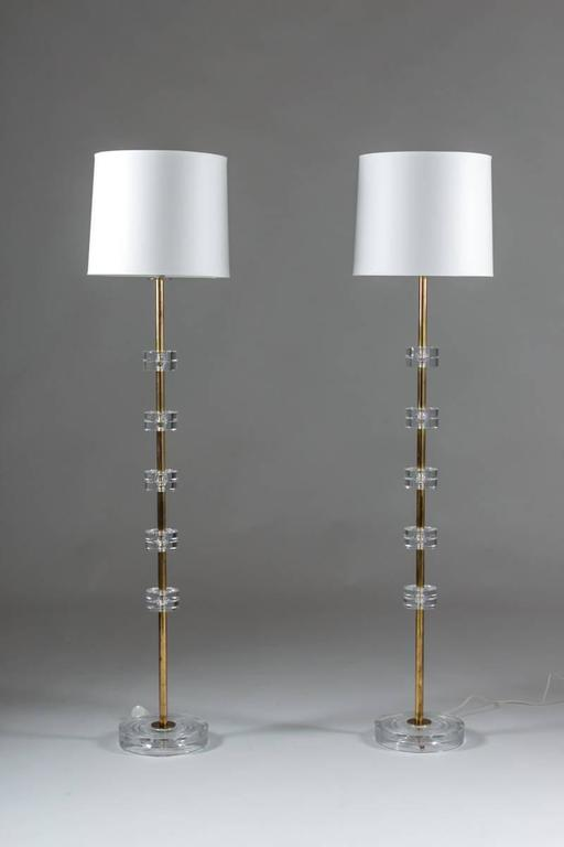 A pair of exclusive floor lamps by Carl Fagerlund for Orrefors. This model is among the best that Carl Fagerlund designed and they rarely appear as floor lamps. They feature crystal glass discs, separated by brass tubes and a bottom plate of crystal