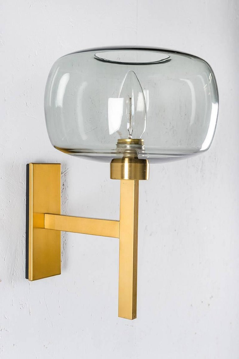 Wall lamps by Holger Johansson for Westal, Sweden. Wall lights of beautiful clean design featuring a rectangular brass frame and a grey-blue glass sphere. The lamps come from a church in Forshaga, Sweden, which was built in the 1960s.  Condition:
