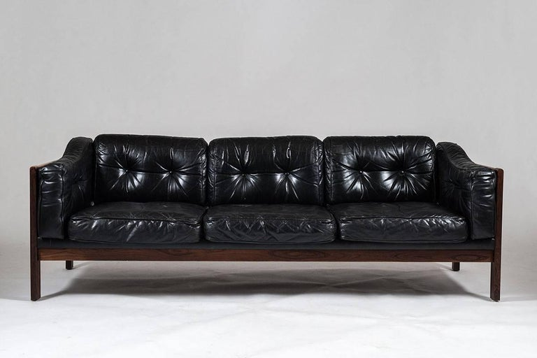 Top-quality sofas designed by Ingvar Stockum for Futura Möbler in 1965. This sofa was only in production for two years because production costs were too high. This luxury version with its frame made of solid rosewood and black leather cushions