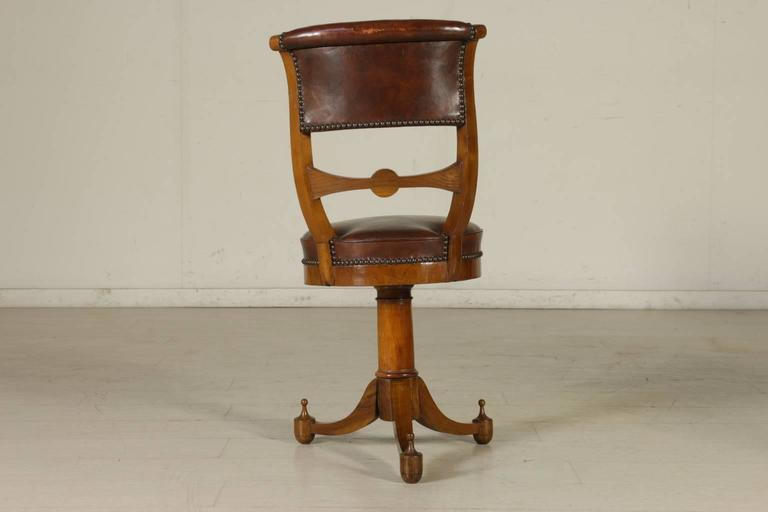 A group of four early 19th century Empire walnut and cherry music chairs with central baluster. Three turned legs ending in a tip. Round padded seats and padded open backrests. Imprinted and gilded leather seat and backrest with Napoleonic coat of