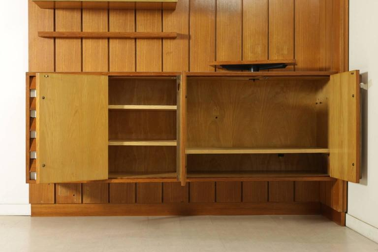 A sitting room cabinet designed for a private client in Milan, composed of wainscoat, closed and open compartments, shelves, adjustable TV stand. Teak veneer, formica, brass, screen printed decorative panel. Manufactured in Italy, 1960s.