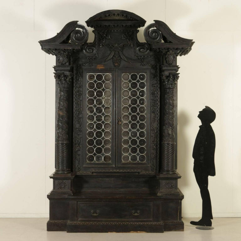 An important Renaissance Revival two-door walnut veneered bookcase with artistic glasses. It features a pair of towers with Corinthian capitals ending in a tripartite tympanum. Richly carved with floral and vegetal patterns and a crown with drapery.