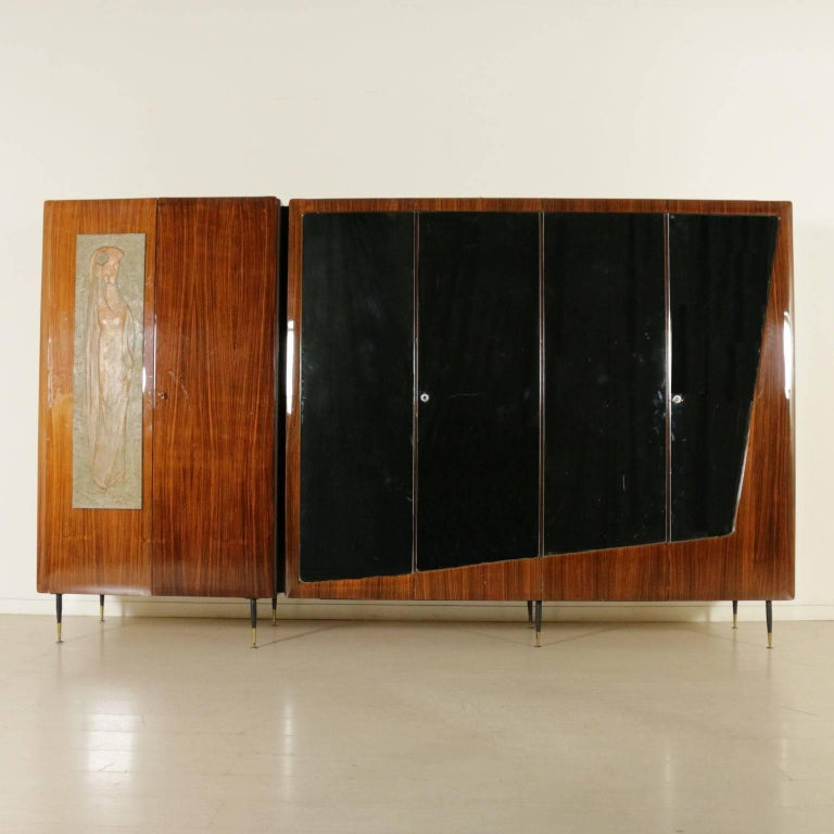 A wardrobe, rosewood veneer with mirrors, decorative wood panel, metal legs with brass ferrules. Manufactured in Italy, 1950s-1960s.