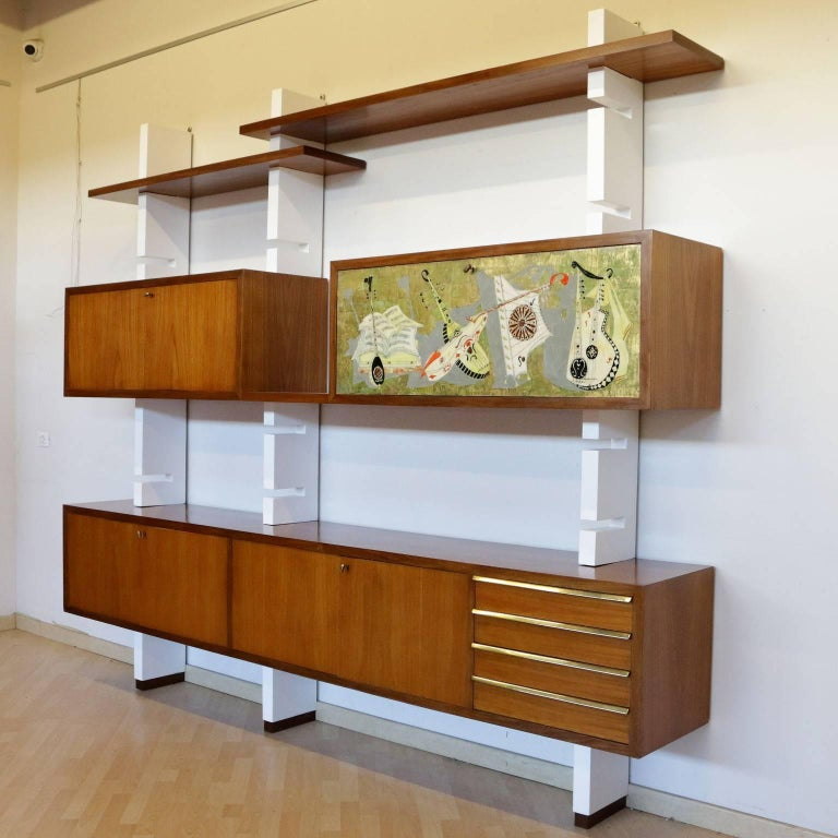 A bookcase with open shelves and containers. Mahogany veneer, lacquered wood uprights, brass and a drop-leaf door with silk-screened drawing. Manufactured in Italy, 1960s.