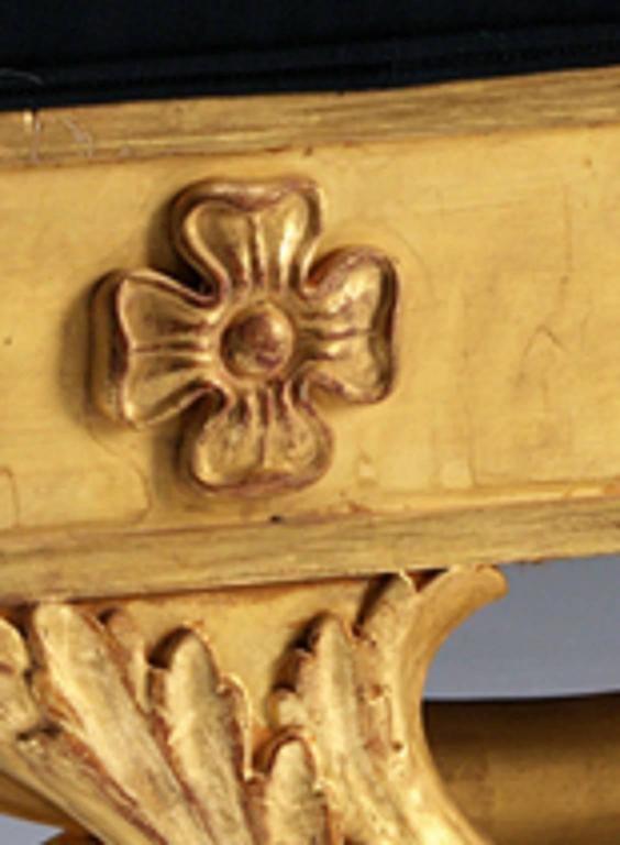 A Regency gilded wood window seat, the panelled frieze inset with carved paterae, supported by a naturalistically carved 'x' frame base. Upholstered in clients own material.