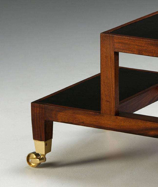 A George III design, mahogany four-step metamorphic library coffee table, with decorative gilt incised leather top and leathered steps opening to form a library step ladder on square brass castors.