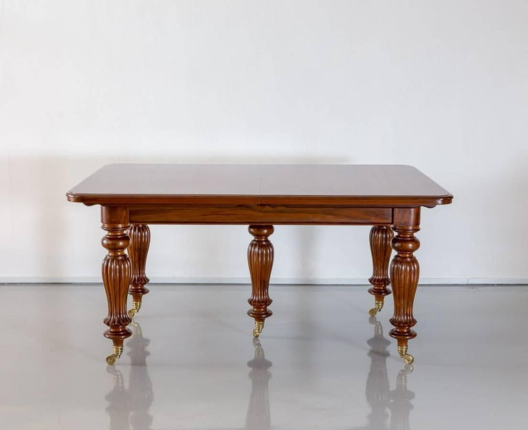 A British colonial teakwood extending dining table with rounded corners. The top, with a deep moulded edge, extends well beyond the base.  The table has a telescopic under-frame that extends via a winding mechanism, which allows the table to be