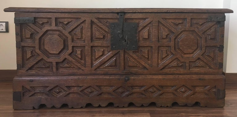 A Spanish 18th century wood coffer. This Spanish trunk from the 18th century features beautifully visible dovetail joints down each corner side and a scalloped skirt which is adorned with geometrical carvings. The trunk's interior offers a large