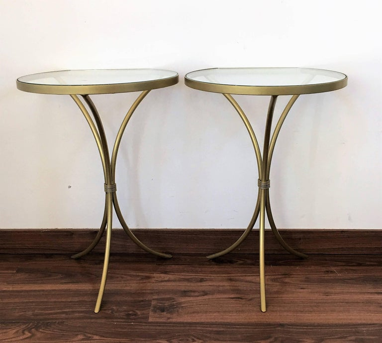 Pair of Italian midcentury glass and brass tripod side, end or nightstands A pair of Italian midcentury hand blown Murano glass side or end tables with round glass tops embedded by large iron finials supported by gold fluted columns resting on gold