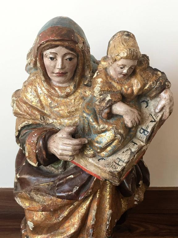 This sculpture represents Santa Ana (Saint Anne) with the infant Mary.  Verge