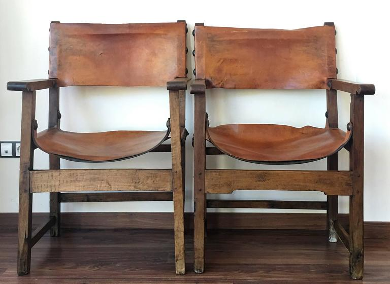 Pair of Spanish Colonial style armchairs, having leather both seats and backs, and brass nailheads.